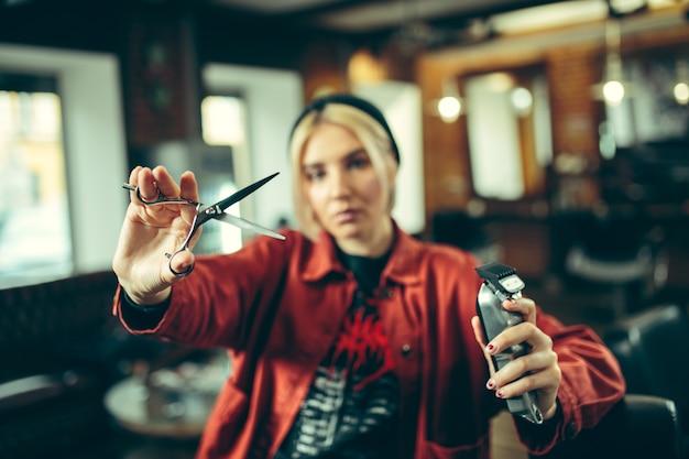 Парикмахерская. женский парикмахер в салоне. гендерное равенство. женщина в мужской профессии. руки крупным планом