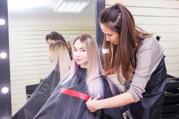 Парикмахерская. парикмахер стрижет волосы девушки ножницами. девушка в салоне красоты, уход за волосами