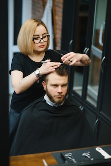 Barbershop. hairstylist cutting client hair in barber shop