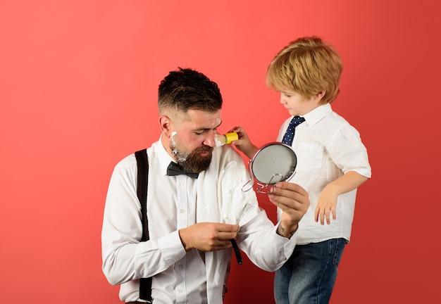 Barbershop little boy holds barber shop scissors hairdresser with razor for shaving barber shop