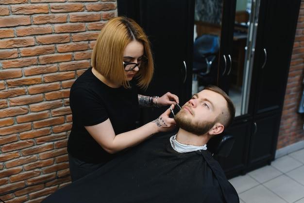 理髪店や美容院のコンセプト。女性美容師ははさみでひげをカットします。長いあごひげ、口ひげ、スタイリッシュな髪の男。