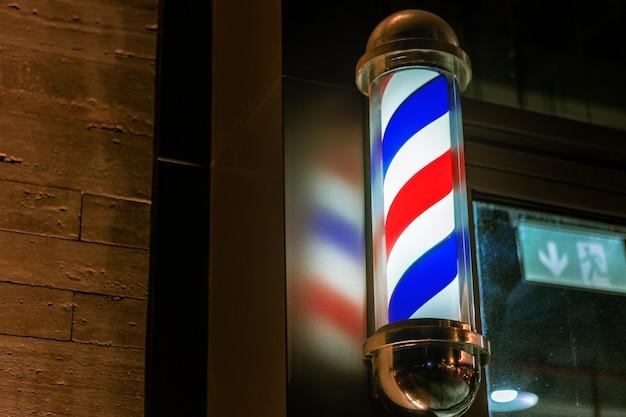 Знак полюса парикмахерской прикреплен к стене здания