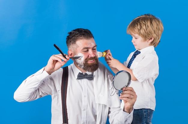 Парикмахерский салон. бородатый мужчина в парикмахерской. парикмахер и парикмахерская концепция. персональный парикмахер-стилист. парикмахерская. семейная парикмахерская. день семьи. отец и сын.