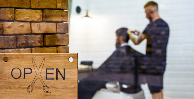 Парикмахерский салон. открытый бардерный магазин. парикмахер или парикмахер. мужчина посещает парикмахера в парикмахерской.
