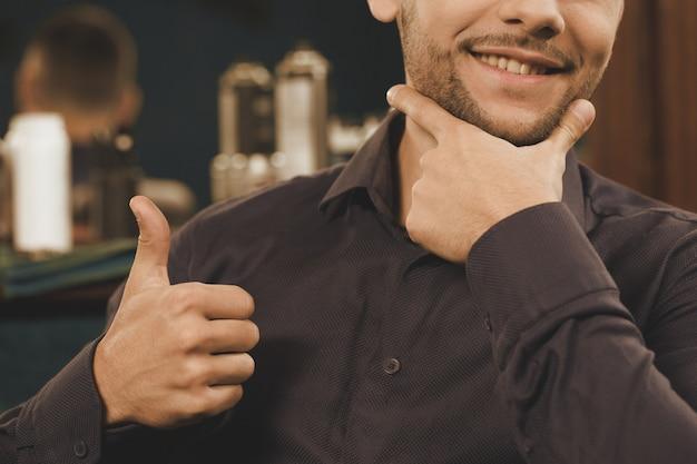 理髪店のルール。広く笑みを浮かべて、親指を現して彼のひげに触れる男のクローズアップをトリミング
