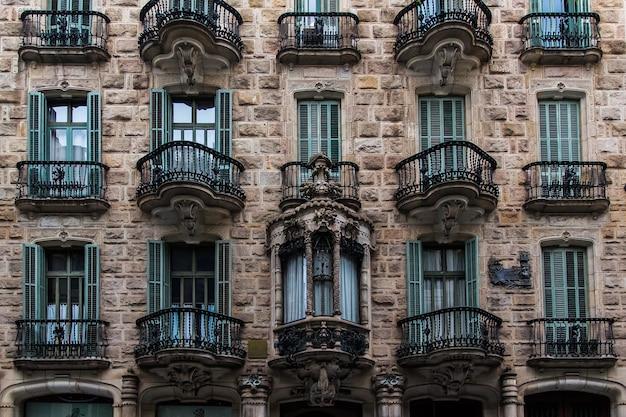 바르셀로나, 카탈로니아, 스페인, 2019년 9월 22일. 외부 역사적 건물의 세부 사항. 창문과 벽에 고대의 부조. 건축 디자인 요소입니다.