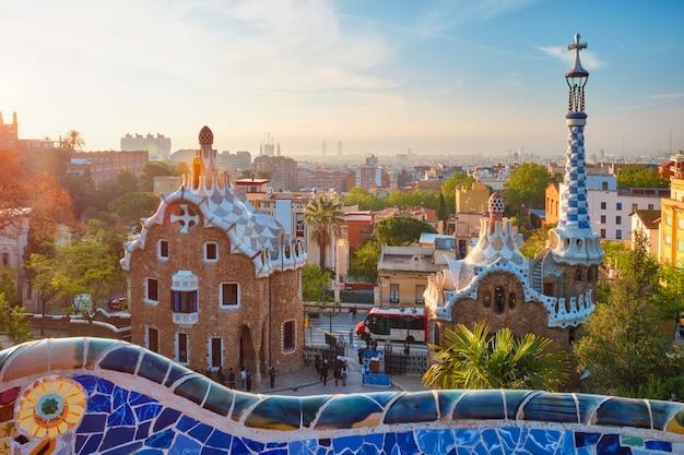 グエル公園からのバルセロナの街の眺めグエル公園のカラフルなモザイクの建物の日の出の眺め