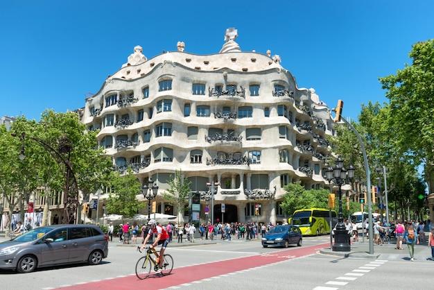 バルセロナ、スペイン-2016年5月21日:スペイン、バルセロナの通りに人々の群衆とカサミラのファサード。アントニ・ガウディによって設計された有名な建物で、ユネスコのリストに含まれています