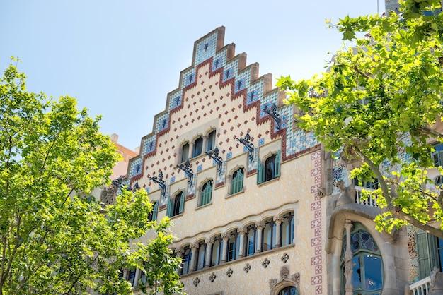 バルセロナ、スペイン-2016年5月21日:スペイン、バルセロナの通りに緑の木々とカサミラのファサード。アントニガウディによって設計された有名な建物で、ユネスコのリストに含まれています