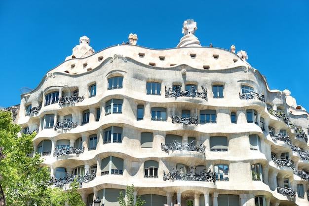 バルセロナ、スペイン-2016年5月21日:スペイン、バルセロナの通りに緑の木々とカサミラのファサード。アントニ・ガウディによって設計された有名な建物で、ユネスコのリストに含まれています