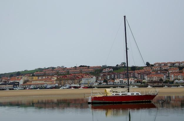 Barco en la mar junto a casas con reflejo