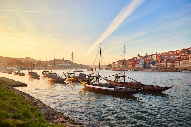 Типичные португальские деревянные лодки, называемые «barcos rabelos», перевозящие бочки с вином по реке дору с видом на виллу нова-де-гайя в порту, португалия