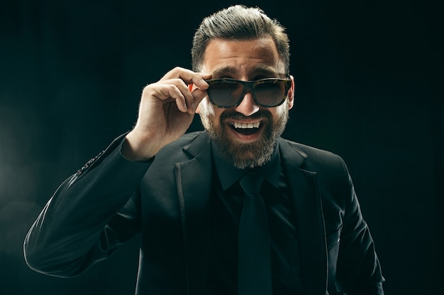 スーツを着た男。黒の背景にスタイリッシュなビジネスマン。美しい男性の肖像画。若い感情的な男。
