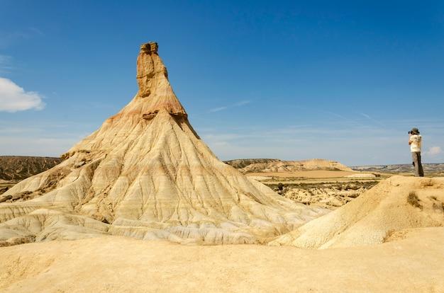 Человек принимая фото в природном парке bardenas reales. туристическая фотография. концепция фотографии.