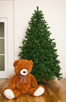 Bare artificial christmas tree with teddy bear