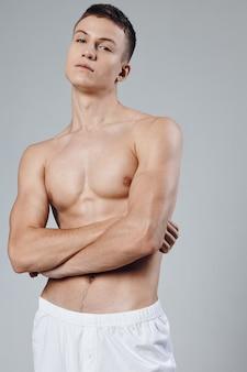 맨 손으로 가슴을 가진 운동 선수가 가슴 위로 팔을 교차하고 팔 근육 모델