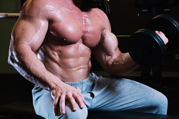 Bare-chested man lifting dumbbell
