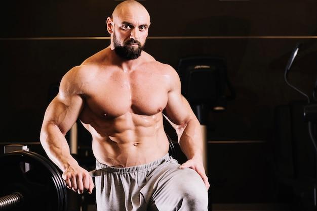 Bare-chestedman posing near barbell