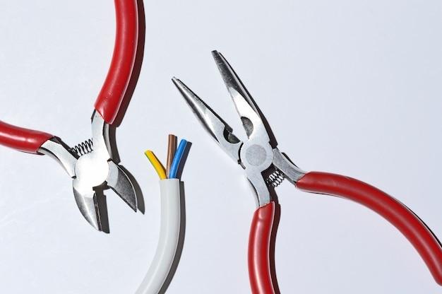 Оголенный электрический провод, кусачки и плоскогубцы не на светлом фоне. верхний вид.