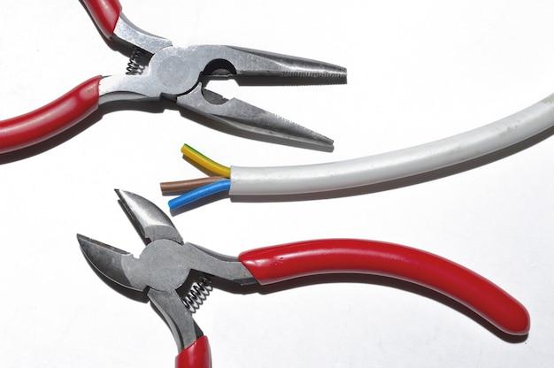 Оголенный электрический провод, кусачки и плоскогубцы