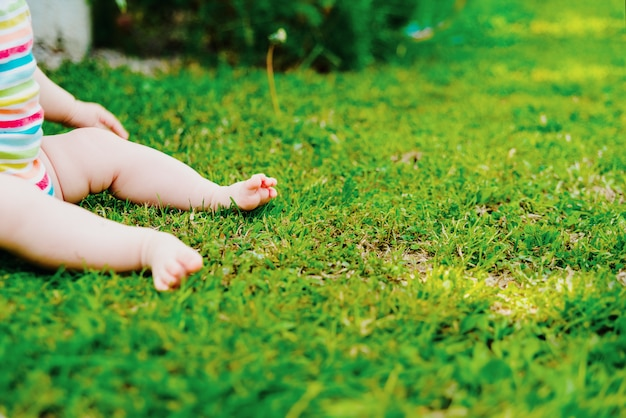 Bare feet of a baby sitting on the grass, with plenty of free space for text.