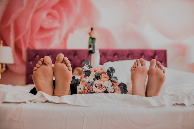 Bare feet of the bride and groom lie on a pink blanket between them lies a wedding flower bouquet.