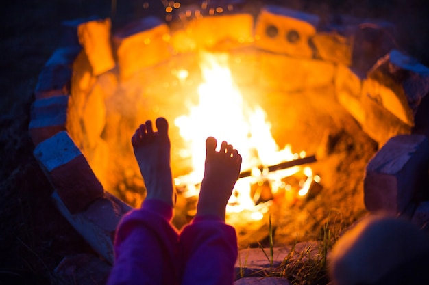 Bare feet of child by fire. gatherings at night by campfire in open air in summer in nature. family camping trip, gatherings around the campfire. camping lantern and tent. warm your feet, cold night