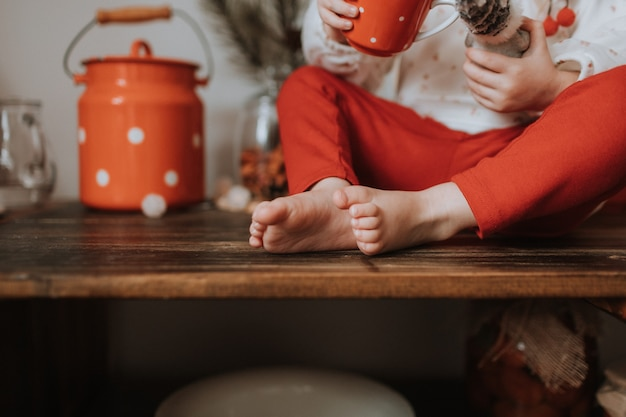Bare feet of a child in red trousers sitting on a wooden chair space for text