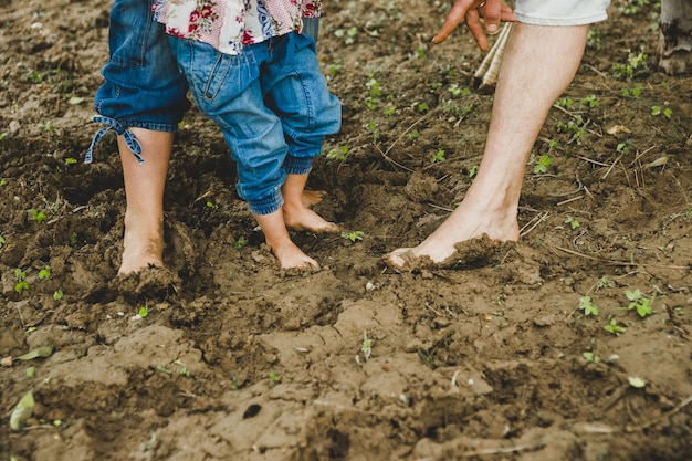 Bare feet of children playing in the mud
