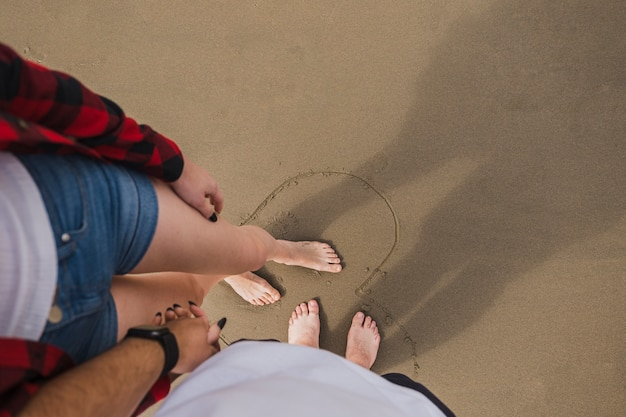 Bare feet couple holding hands on beach