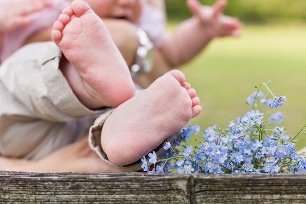 Bare feet of a cute baby and forget me not flowers on the wooden background and a child