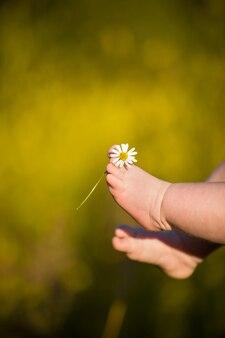 Босые ноги милого ребенка на летнем фоне