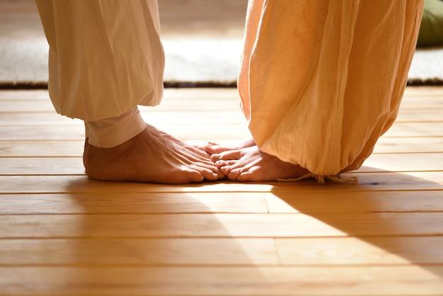 Босые ноги мужчины и женщины занимаются йогой в паре