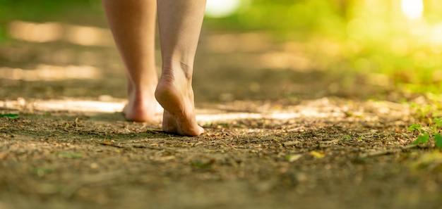 숲에서 흔적을 따라 걷는 여자의 맨발