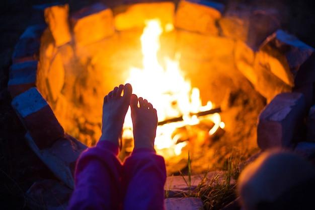 火事で子供の裸足。自然の中で夏に野外でキャンプファイヤーで夜に集まります。家族でのキャンプ旅行、キャンプファイヤーの周りの集まり。キャンプ用ランタンとテント。足を暖かく、寒い夜