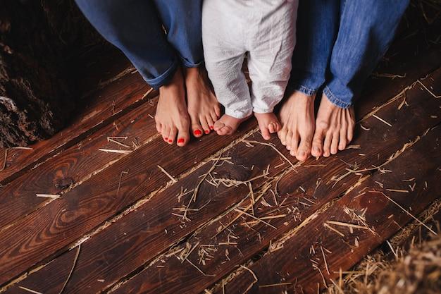家族、母、父と子の素足。木の床