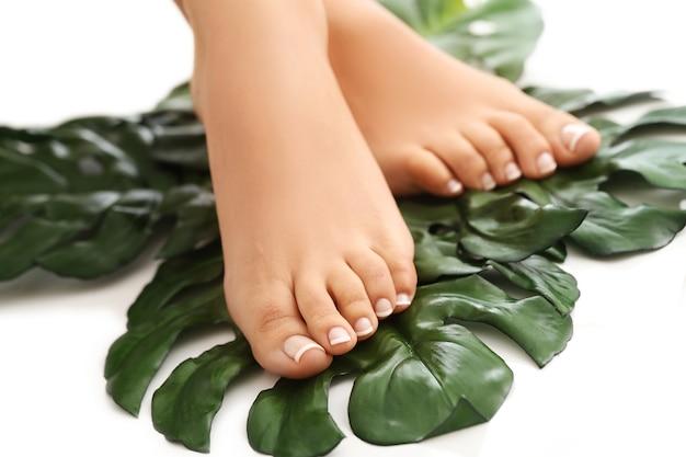 Босые ноги на листьях. концепция ухода за ногами и педикюра