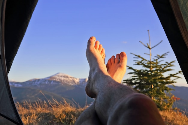 Bare feet resting camper in tent with mountain view