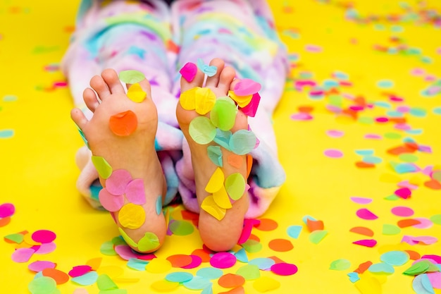 Bare feet of a sitting human in colorful confetti yellow background