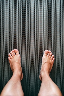 Bare feet and sore feet of mature man, rest on mat