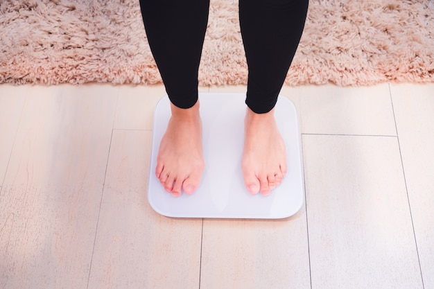 Bare feet women standing on the weight scales