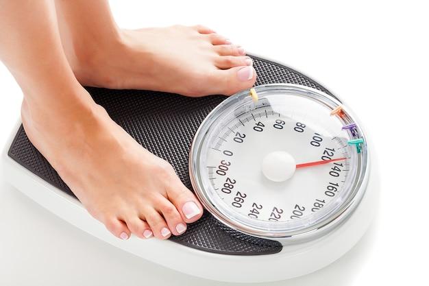 体重計の上に立っている裸の女性の足