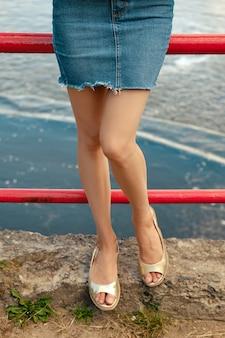 Bare female legs in denim skirt and sandals