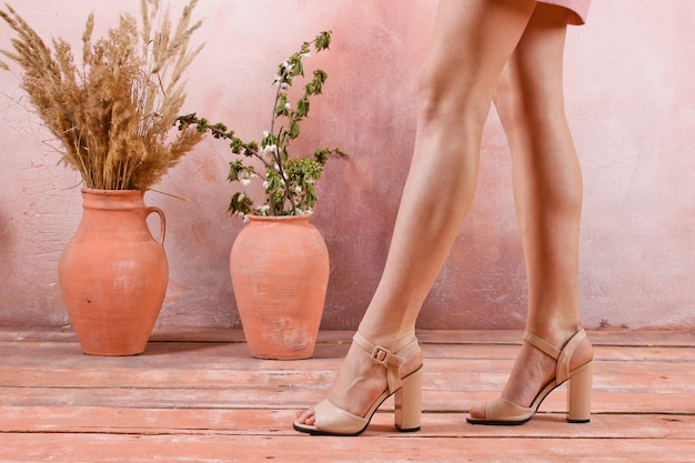 Bare female legs in sandals with heels against the table of a wall with jugs, creative fashion show