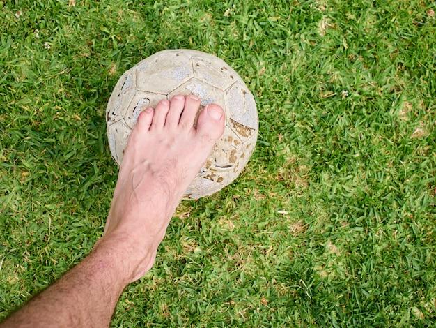 Босая нога человека, стоящего на старой траве, на траве, лица не показаны