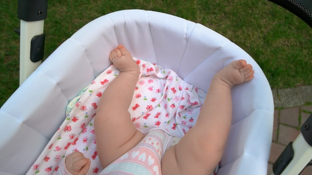 Bare legs of newborn baby girl. sweet infant baby in stroller outdoors. child care concept.