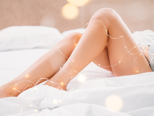 Bare  legs of a woman laying in bed