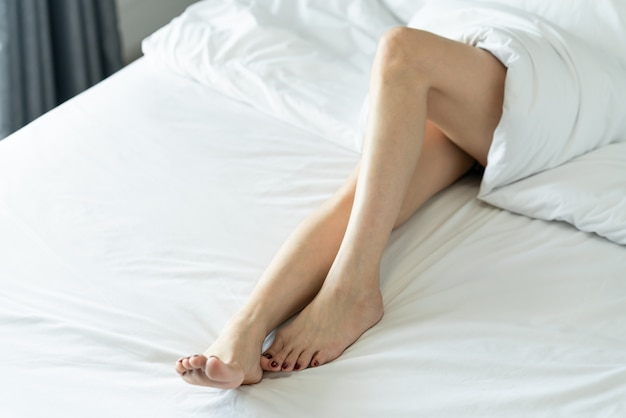 Bare legs of a young woman sleeping on her bed at home