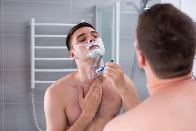벌거벗은 남자가 가슴을 밀고 집에 있는 현대적인 타일 욕실에서 거울을 보고 있다