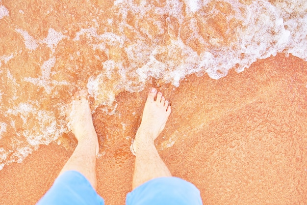 Bare mens feet are washed by sea wave walk along ocean summer vacation man in jeans shorts stands an...